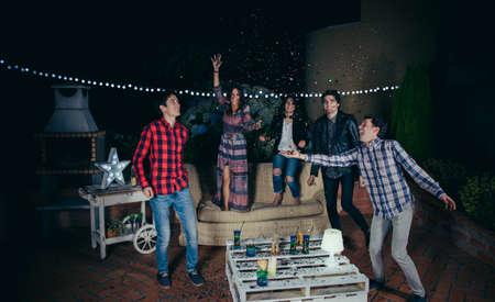 amistad: Grupo de amigos felices jóvenes riendo y divirtiéndose entre el confeti colorido en una fiesta al aire libre. Concepto de la amistad y las celebraciones. Foto de archivo