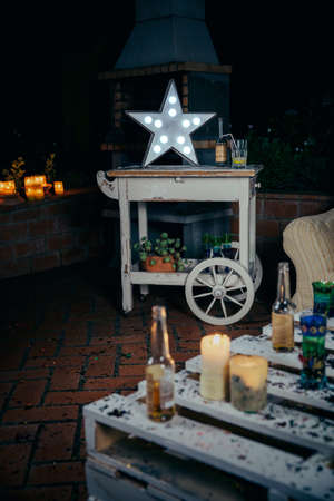 green beer: White handmade star lamp with light bulbs over a wooden cart and pallets table with drinks and confetti in the foreground after outdoors party
