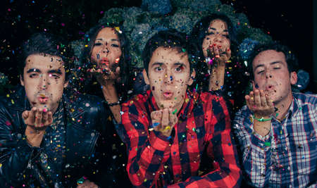 Closeup of young friends group blowing a colorful confetti to the camera in a outdoors party. Friendship and celebrations concept.