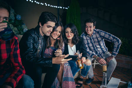 cellular: Group of happy young friends drinking and laughing while looking a smartphone picture in a outdoors party. Friendship and celebrations concept. Stock Photo