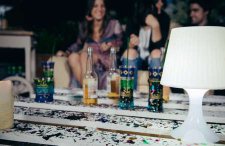 man drinking beer: Closeup of white lamp over a pallets table with drinks and confetti in a outdoors party with people talking in the background. Selective focus on lamp.