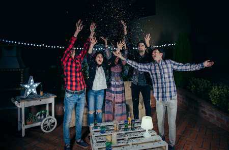 Group of happy young friends raising their arms and having fun among the colorful confetti in a outdoors party. Friendship and celebrations concept.
