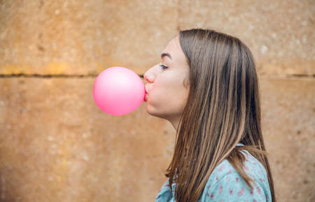 Closeup of beautiful young brunette teenage girl blowing pink bubble gum over a stone wall background Stock fotó