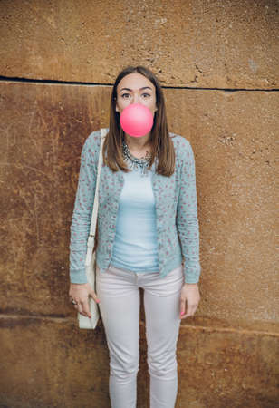 bubblegum: Portrait of beautiful young brunette teenage girl blowing pink bubble gum over a stone wall background