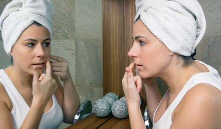 Closeup of young woman with a towel over hair squeezing an acne pimple in her beautiful face in front of a mirror Archivio Fotografico