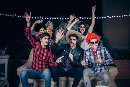 Gruppe glückliche junge Freunde, die Spaß mit Kostümen und atrezzo in einem outdoors party. Freundschaft und Feiern Konzept.