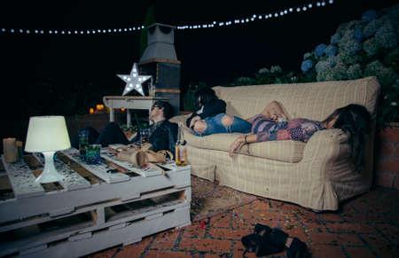 droga: Grupo de j�venes amigos borrachos durmiendo en un sof� despu�s outdoors partido. Diversi�n y problemas con el alcohol y las drogas concepto.