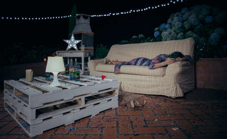 drunk party: Lonely drunk woman holding glass and sleeping lying over a sofa after outdoors party. Fun and alcohol and drugs problems concept.