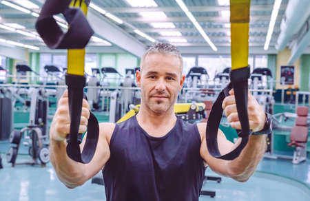 health and fitness: Portrait of handsome man doing hard suspension training with fitness straps in a fitness center. Healthy and sporty lifestyle concept. Stock Photo