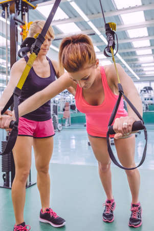 Female personal trainer teaching to woman in a hard suspension training with fitness straps on a fitness center Reklamní fotografie