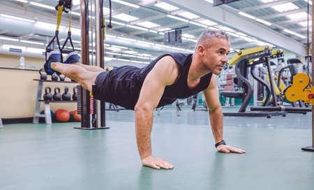 Handsome man doing hard suspension training with fitness straps in a fitness center. Healthy and sporty lifestyle concept. Archivio Fotografico