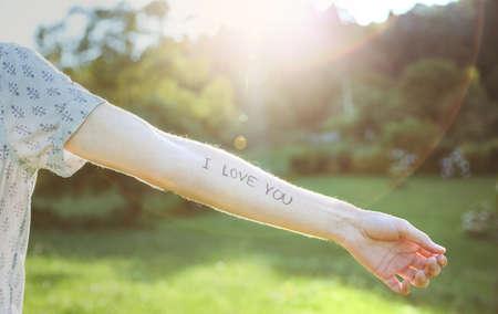 love letter: Primer del brazo masculino con el amor de texto -I Tú- escrito en la piel sobre un fondo de naturaleza soleado