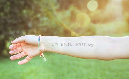 oracion: Primer del brazo femenino con el texto -Estoy todavía en espera- escrito en la piel sobre un fondo de naturaleza soleado