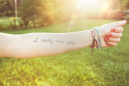 oracion: Primer del brazo femenino con el texto -Yo realmente echo de menos Tú- escrito en la piel sobre un fondo de naturaleza soleado Foto de archivo