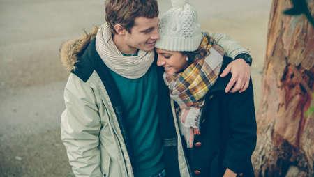frio: Retrato de la joven pareja en el amor con el sombrero y la bufanda abraza y riendo en un frío día de otoño. El amor y las relaciones de pareja concepto.