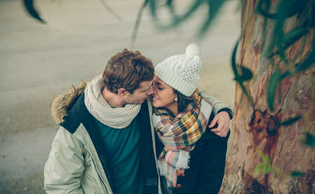 romantic kiss: Portrait of young couple in love with hat and scarf embracing and kissing under a tree in a cold autumn day. Love and couple relationships concept.