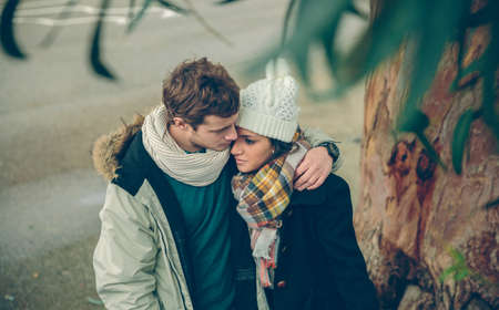 street love: Portrait of young couple in love with hat and scarf embracing under a tree in a cold autumn day. Love and couple relationships concept.