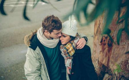 parejas romanticas: Retrato de la joven pareja en el amor con el sombrero y la bufanda abrazando bajo un árbol en un día de otoño frío. El amor y las relaciones de pareja concepto.