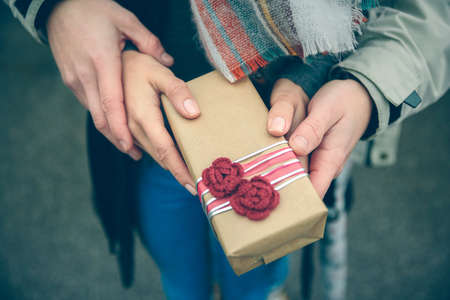flores de cumpleaños: Primer plano de mujer y hombre manos mostrando una caja de regalo con las flores rojas hechas a mano otdoors en un frío día de otoño. El amor y las relaciones de pareja concepto.