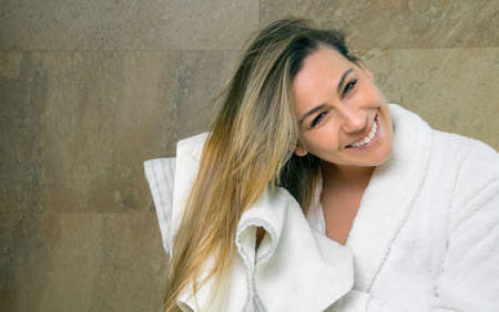 Portrait of beautiful young woman with bathrobe wiping her wet hair with a towel after the shower. Health and beauty concept. Stock Photo