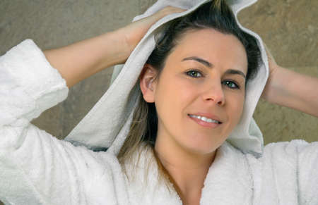Closeup of beautiful young woman with bathrobe wiping her wet hair with a towel after the shower. Health and beauty concept. Stock Photo