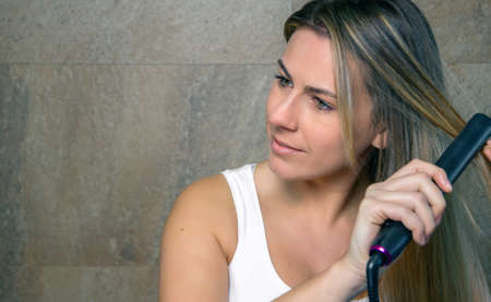 straightener: Closeup of beautiful young woman straightening her hair with a straightener in the bathroom. Health and beauty concept. Stock Photo
