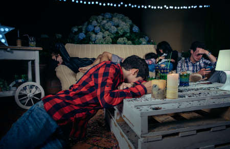 Group of young drunk and tired friends sleeping after outdoors party. Fun and alcoholand drugs problems concept. Stockfoto