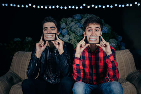two men: Closeup of two funny young men holding smartphones over their faces showing female mouths smiling in the screen on a outdoors party. Friendship and celebrations concept. Stock Photo