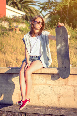 short shorts: Portrait of beautiful young girl with short shorts and skateboard sitting over the wall on a summer day. Warm tones edition. Stock Photo