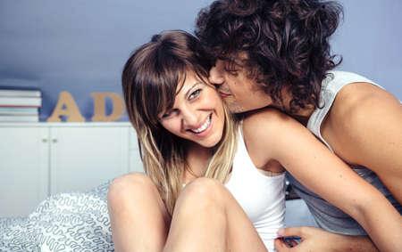 parejas sensuales: Primer del hombre joven y guapo besos y haciendo cosquillas a hermosa mujer riendo sentado sobre una cama. El amor y las relaciones de pareja concepto.