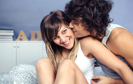 bacio: Primo piano del giovane bello che bacia e che fanno il solletico alla bella donna ridendo seduto su un letto. Amore e relazioni di coppia concetto.