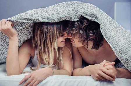 Zbliżenie szczęśliwa młoda para w miłości całuje się pod kołdrą. Miłość i kilka relacji koncepcji. Zdjęcie Seryjne