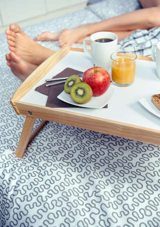 Closeup of healthy breakfast served on a wooden tray ready to eat and couple legs over a bed in the background. Healthy food and home lifestyle concept.