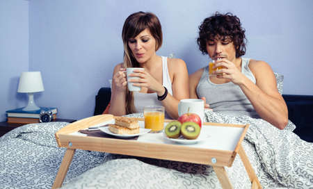 romance bed: Young happy couple in love having breakfast in bed served over a tray at home. Couple home lifestyle concept. Stock Photo