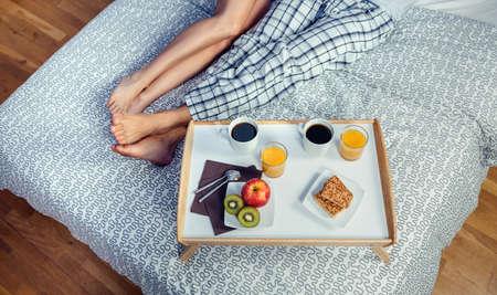 pareja en la cama: Desayuno saludable servido en una bandeja de madera listos para comer al lado de las piernas de par más de una cama. La comida sana y estilo de vida hogar concepto. Foto de archivo