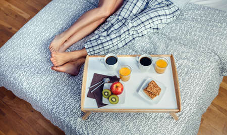 trays: Healthy breakfast served on a wooden tray ready to eat beside of couple legs over a bed. Healthy food and home lifestyle concept. Stock Photo