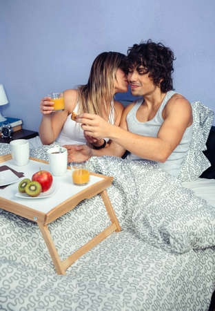 breakfast in bed: Beautiful young woman kissing to man while having breakfast in bed served over a tray at home. Couple home lifestyle concept. Stock Photo