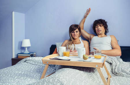 ache: Young couple with stomach pain after eat too much in a weekend breakfast in bed at home