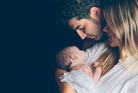 Retrato de la joven pareja feliz abrazando y mirando a su recién nacido sobre un fondo oscuro. La familia y el concepto del cuidado del bebé.