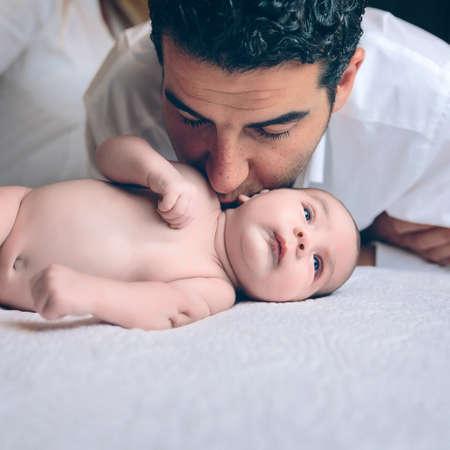 Giovane uomo bello che bacia sul collo per neonato pacifico sdraiato su un letto. Paternità e concetto di cura del bambino.