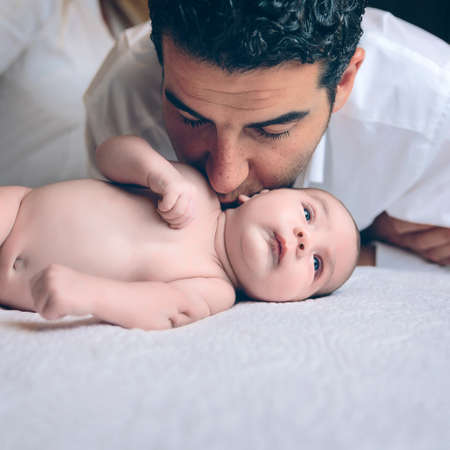 paternity: Young handsome man kissing in the neck to peaceful newborn lying over a bed. Paternity and baby care concept.