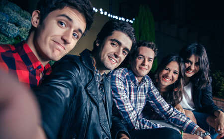 Группа счастливых молодых друзей, улыбаясь, принимая селфи фотографию в открытом воздухе партии. Дружба и торжества концепции. Фото со стока