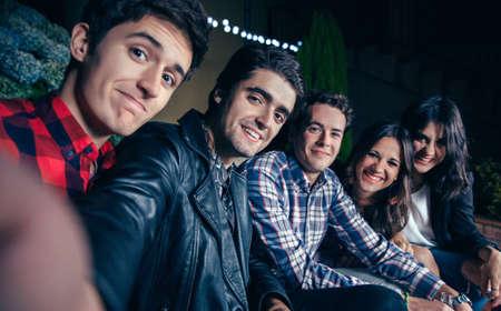 Grupo de jóvenes amigos felices sonriendo mientras toma una foto autofoto en una fiesta al aire libre. Amistad y celebraciones concepto. Foto de archivo