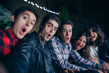 Group of funny young friends shouting while taking a selfie photo in a outdoors party. Friendship and celebrations concept. Stockfoto