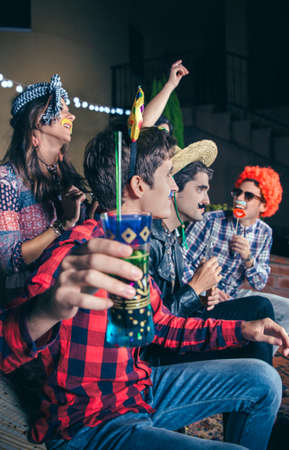togheter: Happy young man with funny bow in his head holding drink and having fun in a outdoors party. Friendship and celebrations concept. Stock Photo