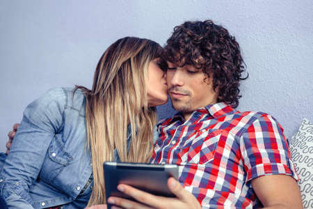 electronic tablet: Portrait of beautiful young woman kissing to handsome man while he looks a electronic tablet. Love and leisure time concept.