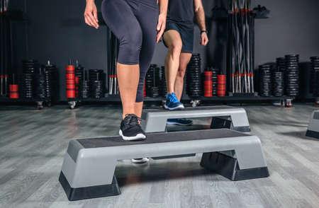 gimnasia aerobica: Detalle de las piernas de los pares sobre la formación tableros paso en clase de aeróbicos en un gimnasio. El deporte y el concepto de salud. Foto de archivo