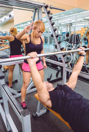 encouraging: Woman personal trainer encouraging to muscle man in a bench press training with barbell on fitness center. Motivation in training concept. Stock Photo
