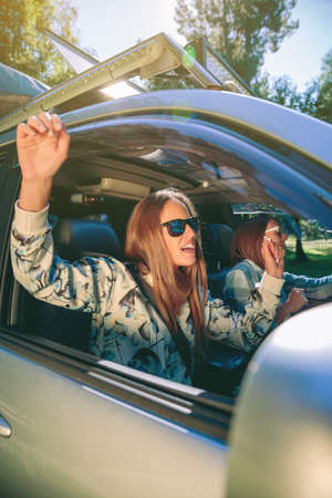 Portrait of happy young woman raising her arms and having fun inside of car in a road trip adventure. Female friendship and leisure time concept. Stockfoto