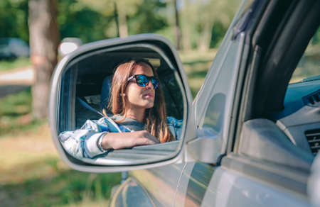 reflection mirror: Reflection in side view mirror of young woman with sunglasses driving car over a nature background